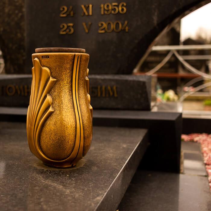 Бронзовая ваза, установленная на гранитное плите памятника из темного камня