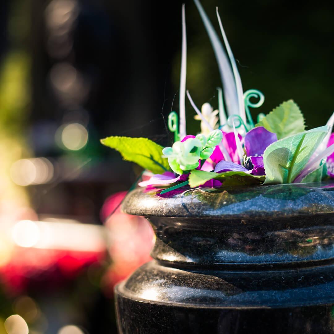 Ваза на кладбище с искусственными цветами